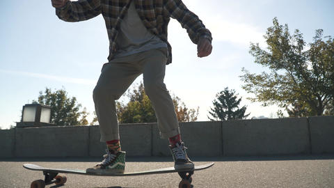 Young guy in a plaid shirt rides a skateboard outdoors. Hipster boy drives on a Live Action