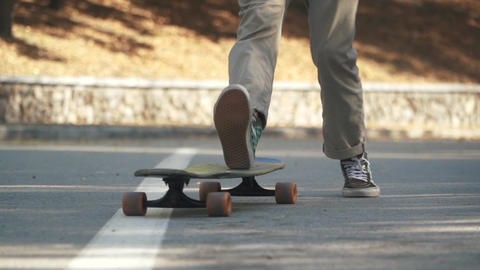 Feet of a guy jumping on a skateboard. Skateboarder guy doing a skateboard trick Footage