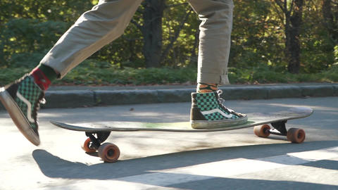 Male feet doing trick on a skateboard. Legs of guy skating on a skateboard Footage