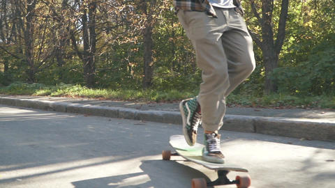 Feet of a guy doing trick on a skateboard outdoors. Legs of skateboarder guy Live Action