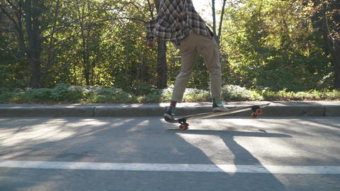 Attractive young man riding skate board. Hipster guy in a plaid shirt Live Action