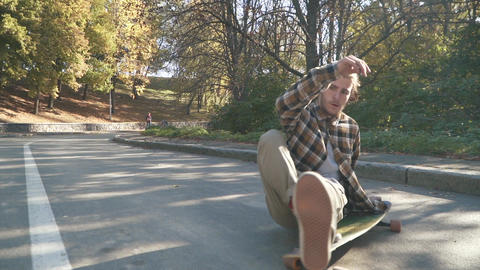 Skateboarder rides lying on a skateboard. Hipster young guy in a plaid shirt Footage