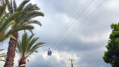 Ropeway teleferic cabin on the background of palms and clouds Live Action