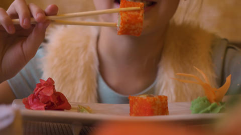 Young teenager girl eating sushi roll with chopsticks in japanese cafe close up Live Action