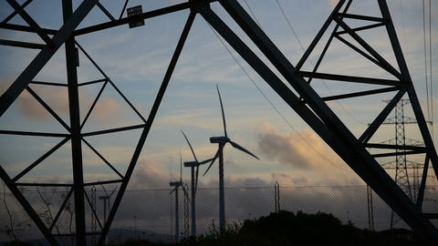 Windmill blades seen through an electricity pylon frame at sunset. Sardinia, Ita ビデオ