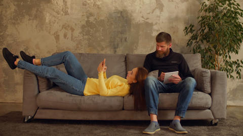 Millennial couple relaxing on sofa in loft apartment Footage
