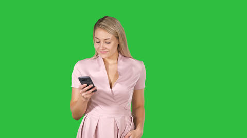 Sexy woman walking and texting on the smart phone on a Green Screen, Chroma Key Footage