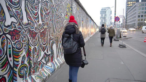 BERLIN, GERMANY - NOV 22, 2018: Woman with a camera walks near Berlin Wall. Slow Live Action
