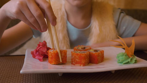 Young caucasian girl eating sushi food in Japanese restaurant with sticks Footage