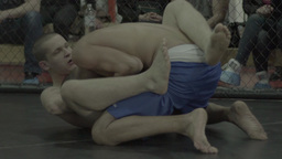 Two fighters during a fight in a cage. Octagon. MMA. Slow motion Footage