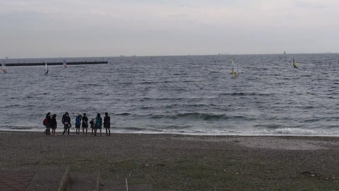 Hi-school girls watching windsurfing in Inage Beachfront Park Footage
