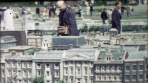 1962: Man enjoying realistic mini model wealthy home replica buildings Footage