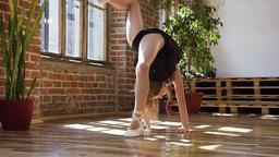 Gymnastics school or ballet school. Cute gymnast girl performs a backflip with Live Action