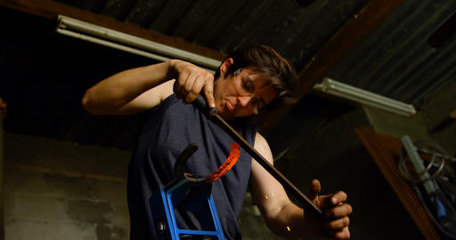 Female metalsmith shaping horseshoe in factory 4k Live Action