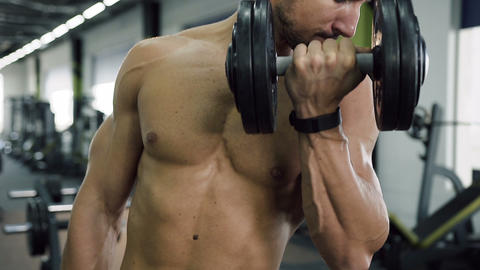 Hard working man with naked torso working out with dumbbells for pumping muscle Footage