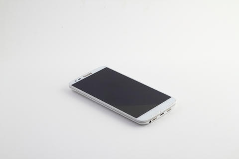 White mobile phone isolated on white background. Phone on the table. Shiny phone Photo