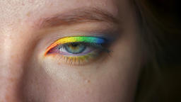 Rainbow makeup on closeup blue eye of caucasian girl looking at camera and Footage