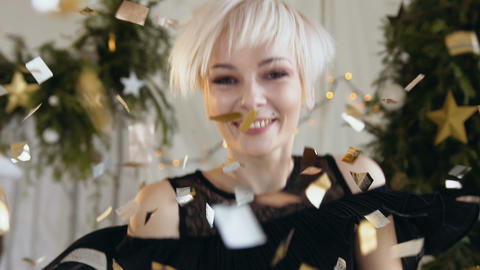 Beautiful young woman is dancing among golden confetti, Charming blonde woman Footage