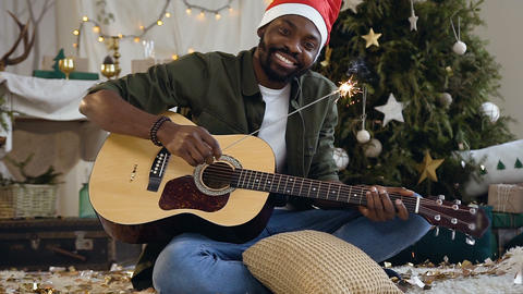 Handsome afro american guy with guitar and bengal light happy is sitting on the Footage
