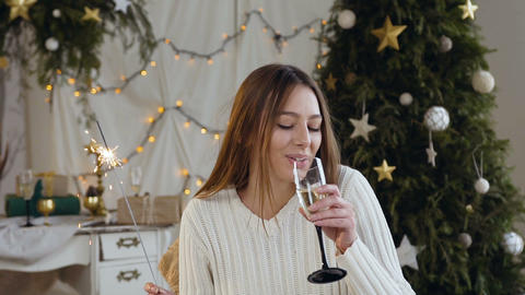 Young smiling woman with long hair celebrating New Year with sparkling wine and Footage