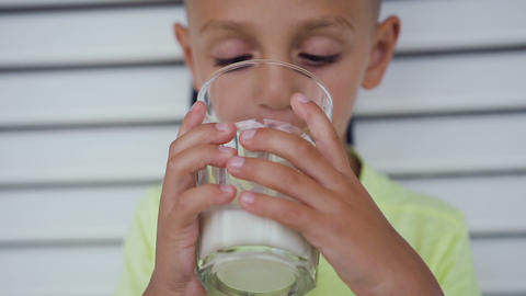 Little cute boy is drinking milk at morning. Cute caucasian child drinking milk Footage