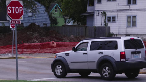 Static shot of a car coming to a brief stop at a stop sign in a residential zone Live Action