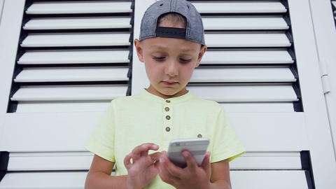 Young teenager in cap playing game on smartphone, isolated on white door Footage