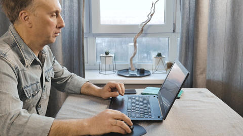 A middle aged man working on a laptop. Freelancer works at home. Side view Footage
