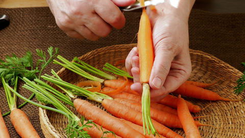Root vegetable. Closeup woman's hands peeling carrot Live Action