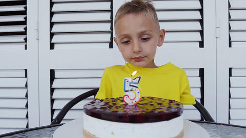 Cute little boy is happily blowing candles on his birthday cake. Happy little Footage