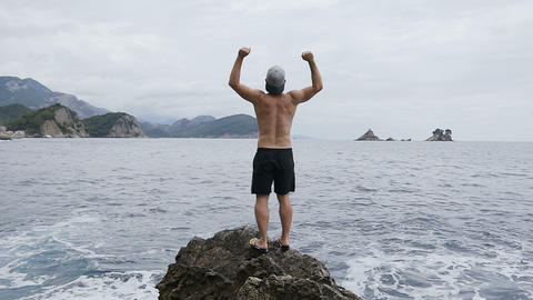 Young man raising hands to the sky standing on rocks by sea. Cheerful man Footage