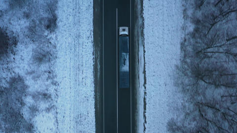 Aerial view of traffic on the road passing through the winter forest in winter ビデオ