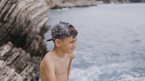 An attractive guy in a cap sits on a rock on the... Stock Video Footage