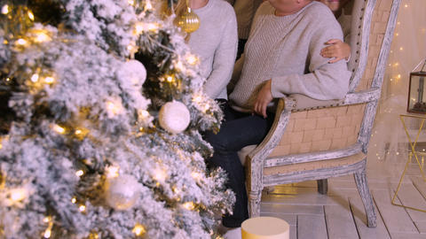 Smiling family having fun near decorative New Year tree at holiday in cozy home Footage