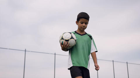 Portrait shot of cute boy walking with soccer ball Live Action