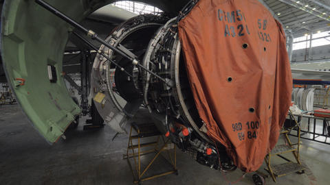 Disassembled jet engine in repair hangar Live Action