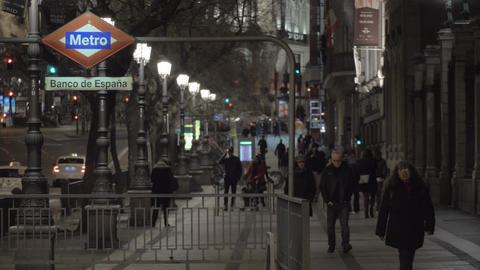 Night view of people walking on sidewalk with subway entrance in night Madrid Live Action