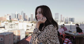 Young adult female looking out across city at a rooftop party and then smiling Footage