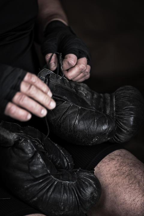 athlete puts on black leather boxing gloves Fotografía