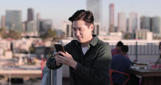 Young adult male messaging friend from a rooftop party Footage