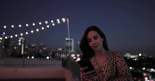 Young adult female looking at smartphone on a rooftop at night ビデオ