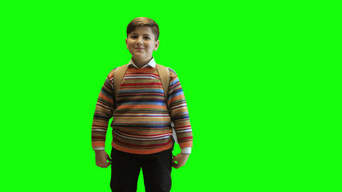 Schoolboy boy in a sweater and with a backpack laughs on a green background GIF