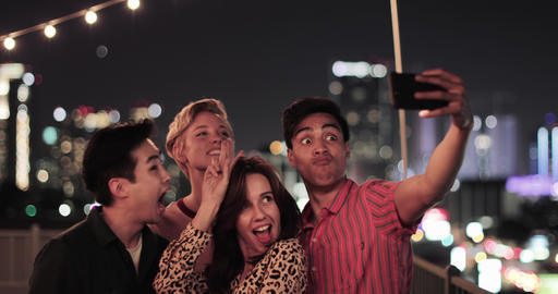 Group of friends taking selfies with city skyline at night ビデオ