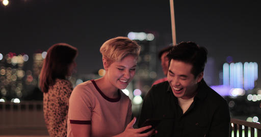 Young adult couple taking selfie with city skyline at night, ライブ動画