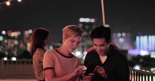 Young adult couple taking selfie with city skyline at night 動画素材, ムービー映像素材