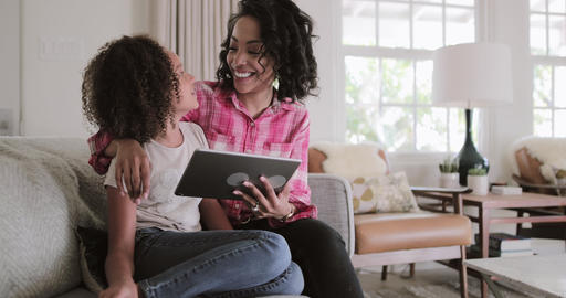 African American mother and daughter watching entertainment on digital tablet at Live Action