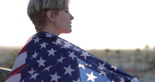 Young adult female wrapped in American flag looking out across city skyline Footage
