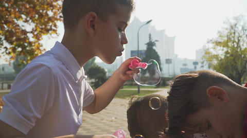 Young boy blowing soap bubbles in autumn park. Boy playing with friends outdoors Live Action