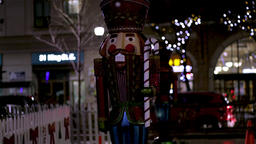 Large nutcracker holding a candy cane Christmas decoration display in the city Footage