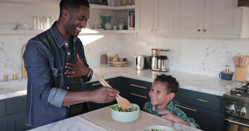African American boy helping father prepare healthy meal in kitchen Footage